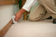 Man cleaning baseboards with a cloth.